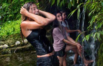 ジャングルの小さな滝を浴びて喜ぶ参加者