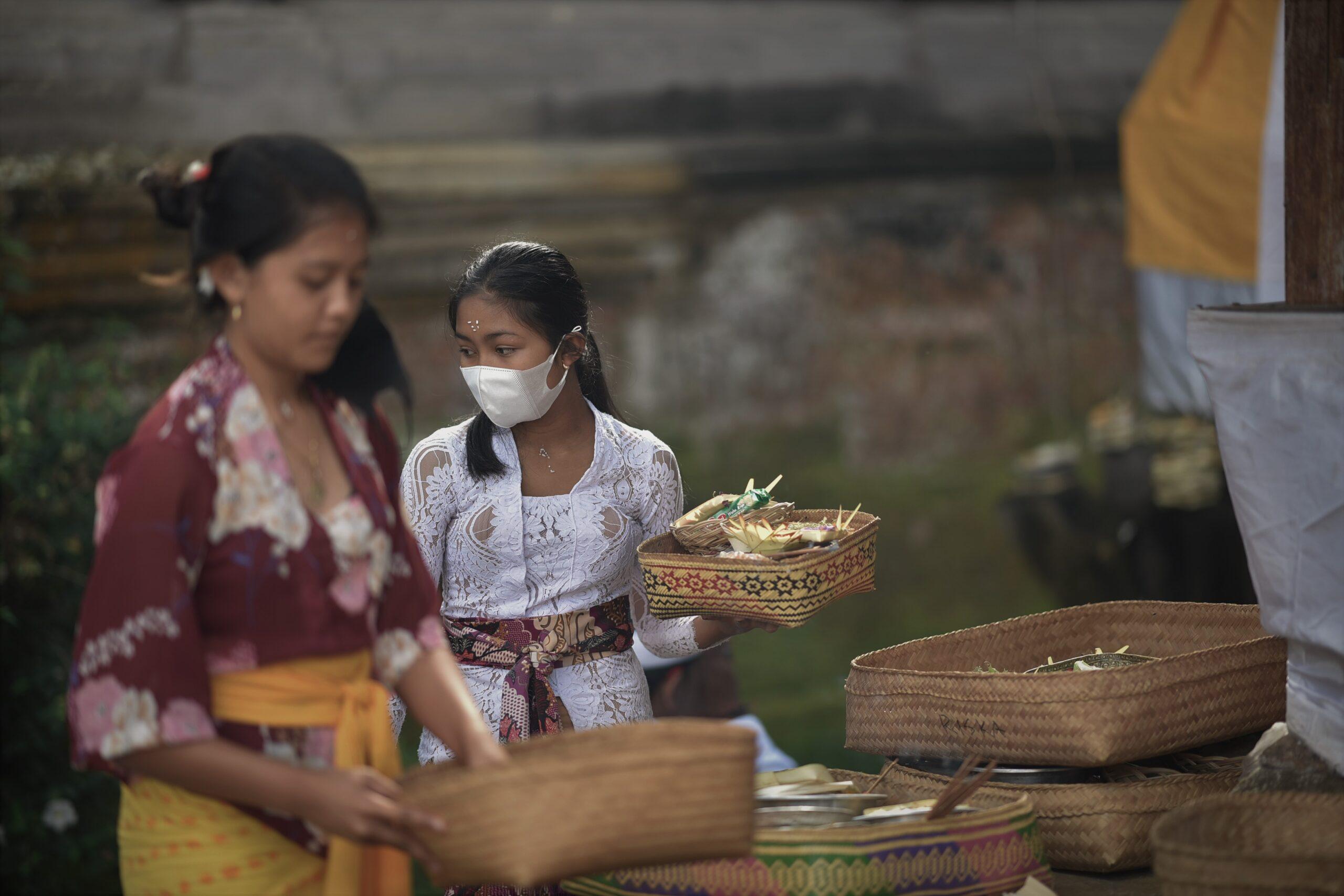 お寺でお供え物の準備をする少女
